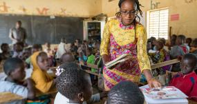 "A teacher trainee helps out in the class two classroom by passing out textbooks. As part of her training she will spend three weeks observing and working with each teacher in the school. Sandogo ""B"" primary school, District 7, Ouagadougou.Credit: GPE Kelley Lynch"